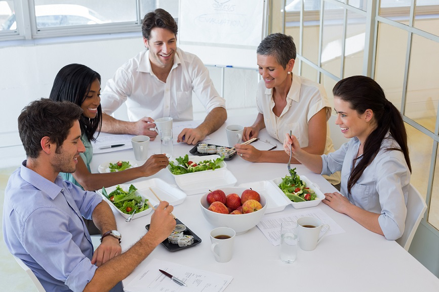 Workers eating fruit and salad together for lunch