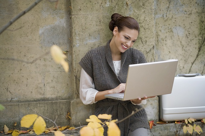 Young happy businesswoman using laptop in yard