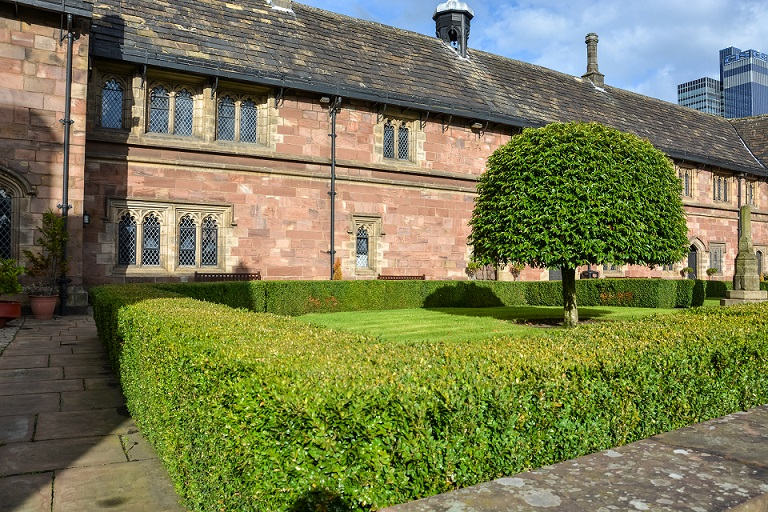 A nice square with trees and hedges next to Chetham's library in Manchester on a sunny day
