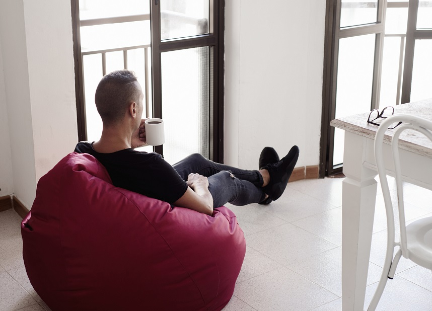 a young man indoors have a coffee sitting in a comfortable red bean bag chair