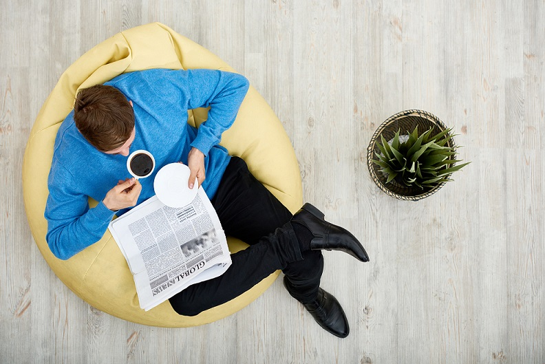 Directly above view of young man wearing blue sweater sitting on cozy beanbag chair, reading newspaper and enjoying fragrant coffee