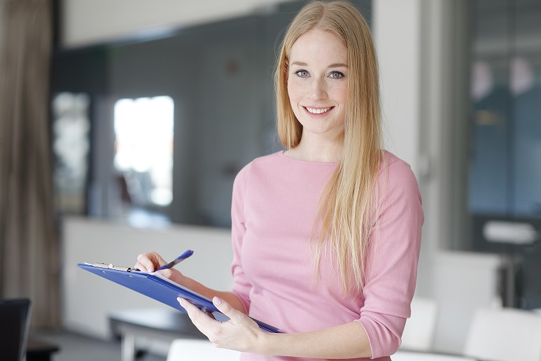 Shot of a young sales woman making notes while standing at office and working.