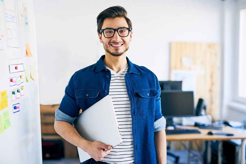 Happy young man, web designer standing with laptop