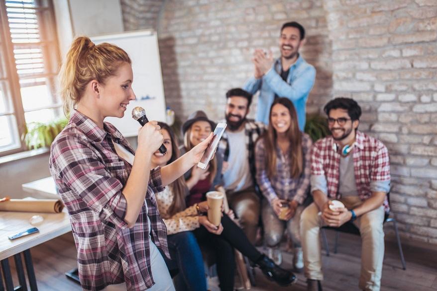 Business people singing karaoke in modern office